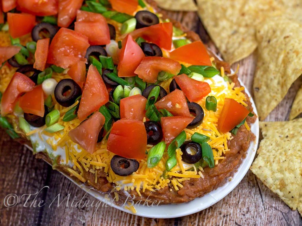 Mexican Seven-Layer Dip | bakeatmidnite.com | #dip #mexicanlayereddip #bhg #christmas